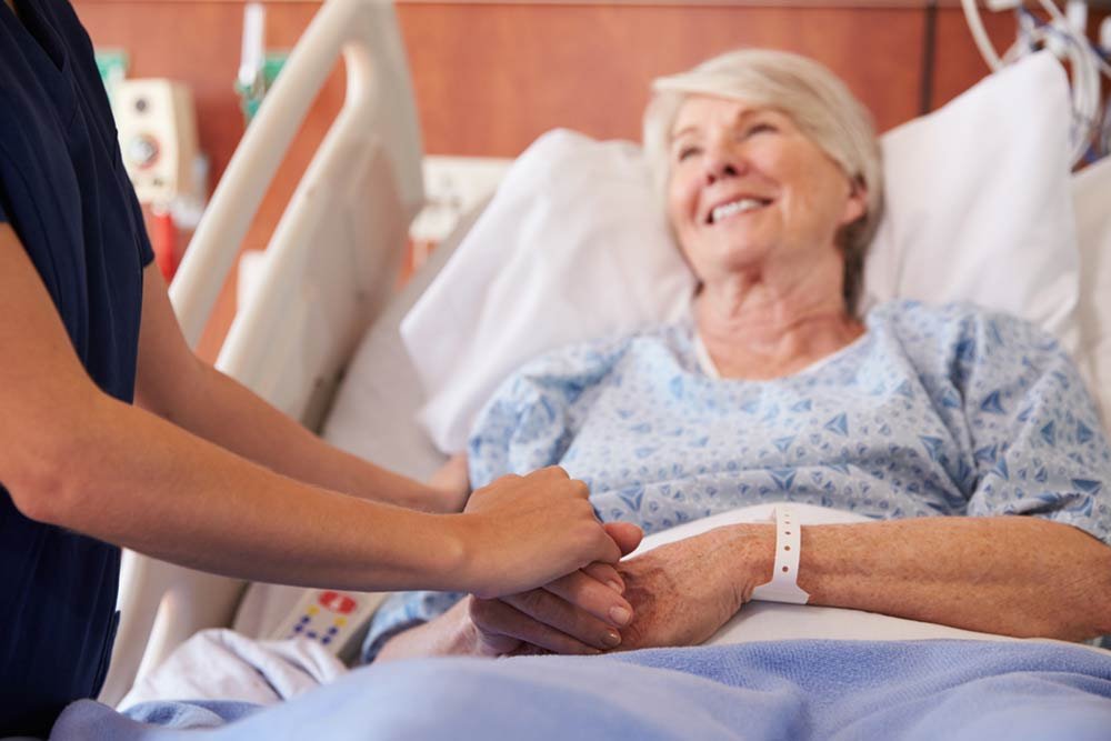 Close Up Of Hospital Nurse Holding Senior Patient's Hand