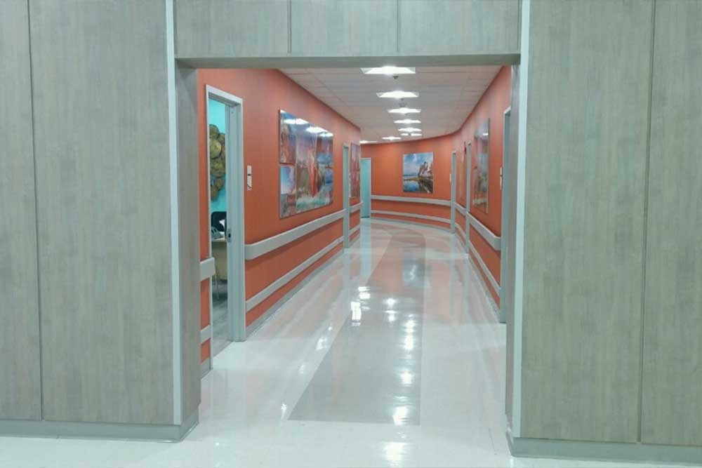 A long corridor with doors to patient rooms and offices at Morningside. Orange walls and shiny floor.